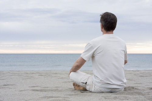 Man meditating on beach